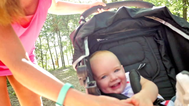 Adorable baby laughing at mom while riding in stroller at park video