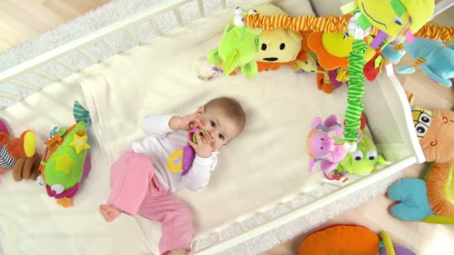 stockvideo's en b-roll-footage met hd crane: adorable baby lying in crib - baby toy