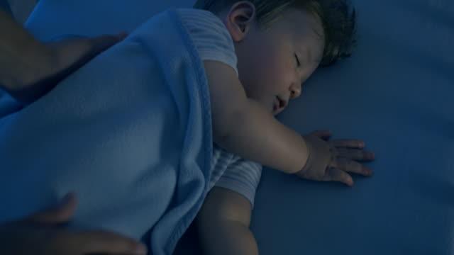 bedårande bebis fredligt sova i sin spjälsäng - baby sleeping bildbanksvideor och videomaterial från bakom kulisserna