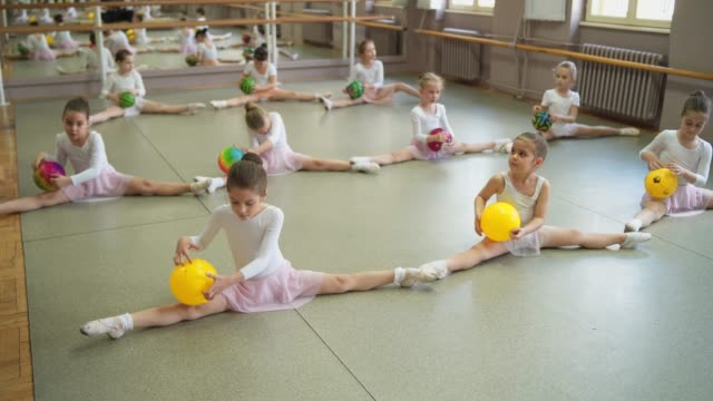Adorable ballerinas doing splits Group of young girls practicing ballet in ballet studio doing the splits stock videos & royalty-free footage