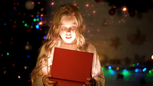 Adorable blond girl opening gift box, magic Christmas atmosphere, glowing effect Adorable blond girl opening gift box, magic Christmas atmosphere, glowing effect paranormal stock videos & royalty-free footage