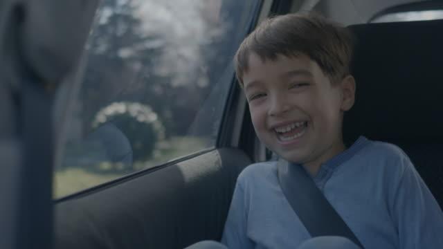 urocza chłopiec śmiejąc się podczas jazdy samochodem - mebel do siedzenia filmów i materiałów b-roll