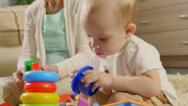 自宅で一緒に遊んで愛らしい子供と祖母 ビデオ