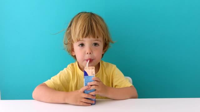 vídeos y material grabado en eventos de stock de adorable niño bebiendo de la caja a través de la paja - zumo