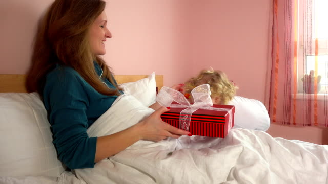 Adorable child girl bring present gift box to her mother in pajamas video