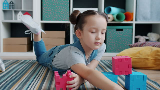 Adorable child playing with toys lying on house floor concentrated on intelligent game video