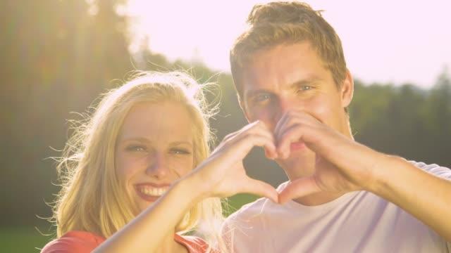 vídeos de stock e filmes b-roll de portrait: adorable couple makes a heart shape with fingers during outdoor date. - sorriso aberto