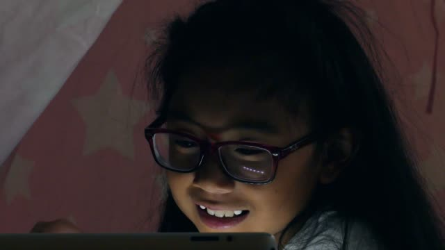 vídeos de stock e filmes b-roll de adorable elementary age girl uses digital tablet while in homemade fort - etnia filipina
