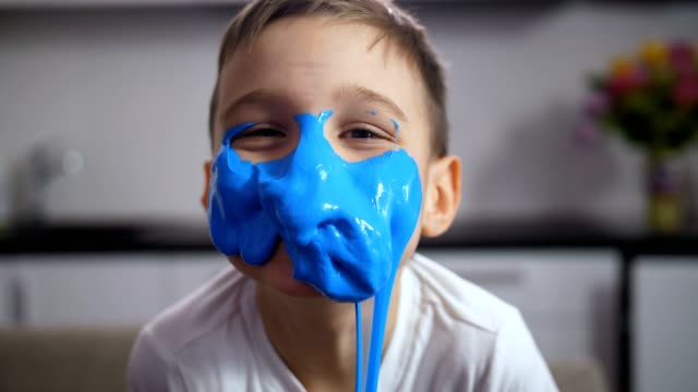 adorable funny boy with face covered blue slime - предподростковый возраст стоковые видео и кадры b-roll