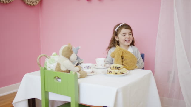 Adorable girl having a tea party with her stuffed animals Adorable girl having a tea party and laughing with her stuffed animals indoors princess stock videos & royalty-free footage