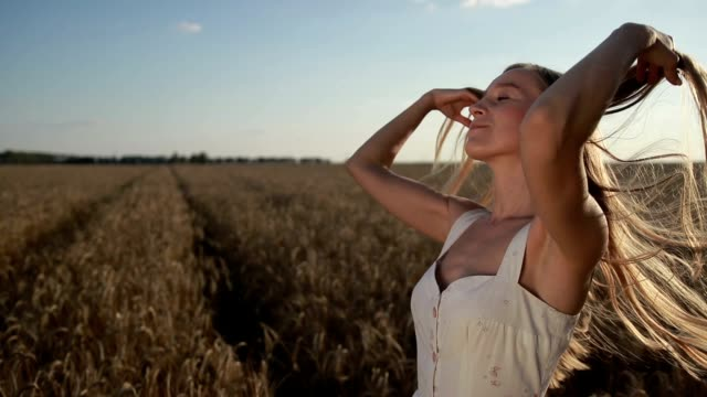 Adorable girl playing with hair in cereal field video