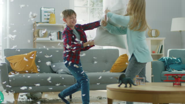 vídeos de stock e filmes b-roll de adorable little boy and sweet little girl have a pillow fight in the sunny living room. siblings having fun fighting with pillows, feathers flying around. in slow motion - sala
