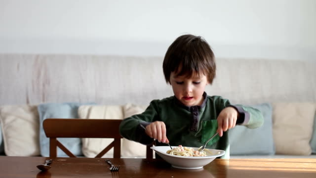 Adorable little boy, eating spaghetti at home, homemade pasta video