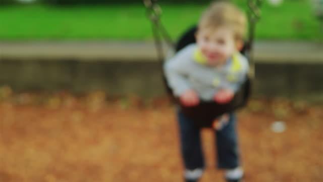 entzückender kleiner junge auf einer schaukel in zeitlupe, mit einem großen lächeln auf seinem gesicht - kind schaukel stock-videos und b-roll-filmmaterial