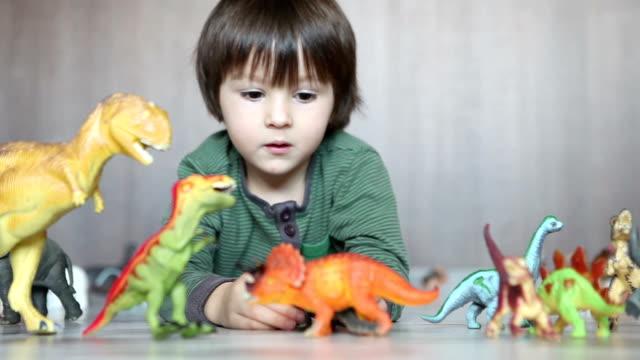 adorable little boy, playing with plastic animals and dinosaurs on the floor - dinosaurie bildbanksvideor och videomaterial från bakom kulisserna