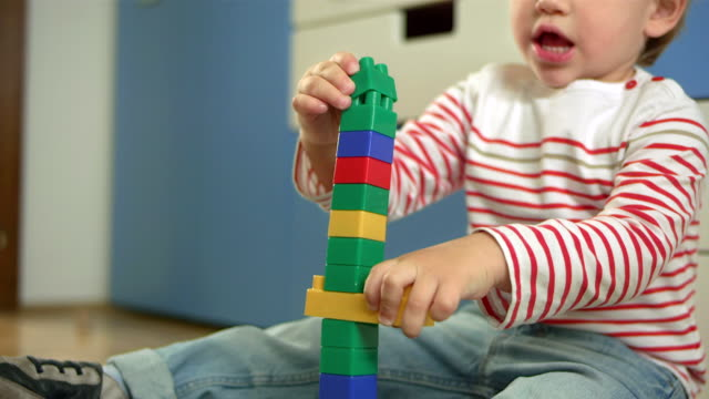 adorable little boy stacking up blocks - lego stok videoları ve detay görüntü çekimi