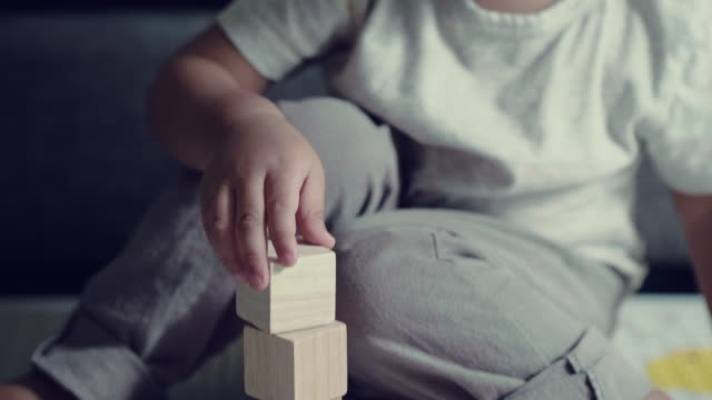 adorable little boy stacking up blocks - giocattolo video stock e b–roll