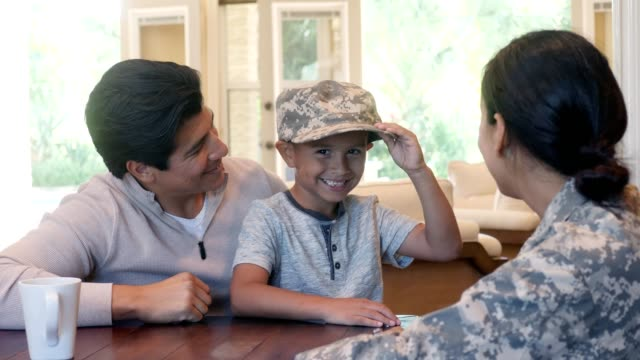 adorable little boy wears his mom's military uniform hat - military lifestyle stock videos & royalty-free footage