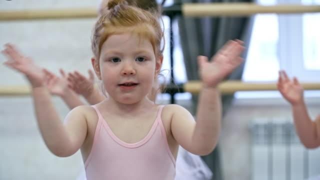 bedårande liten flicka klappa händerna - gympingdräkt bildbanksvideor och videomaterial från bakom kulisserna