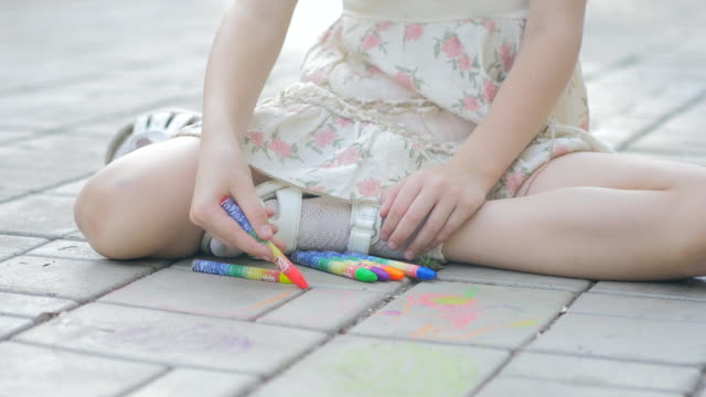 Adorable little girl drawing outside with chalk video