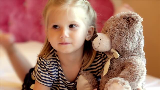vídeos de stock e filmes b-roll de adorável menina abraçar sua ter - teddy bear