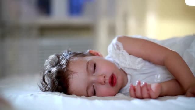 Adorable little girl in a white dress sleeping with her toys. Dolly shot.