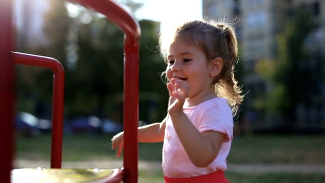 adorable little girl on playground in autumn park - solo una bambina femmina video stock e b–roll