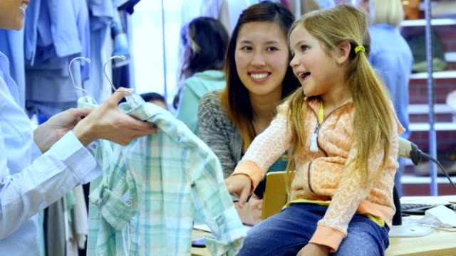 Adorable little girl picks out shirt at clothing store Beautiful Caucasian little girl smiles while choosing a shirt at a clothing store. Her mother or sales clerk holds up two shirts and the girl points to one of the shirts. An Asian female sales clerk is standing behind the girl. Shoppers are browsing in the background. department store stock videos & royalty-free footage