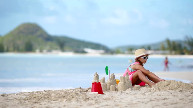 Adorable little girl playing with toys on beach vacation video