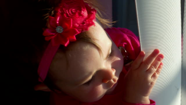 Adorable little girl plays with blinds at window video