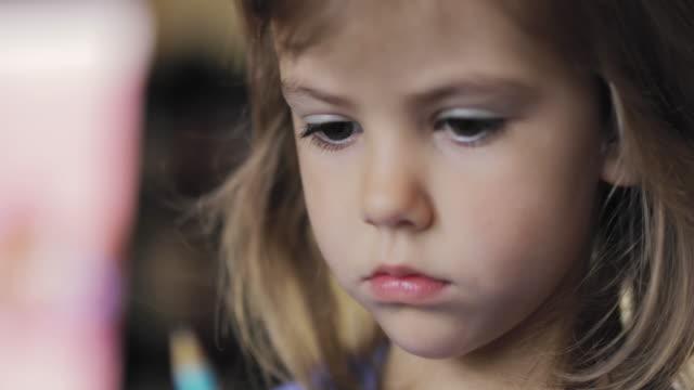 bedårande liten flicka sitter och leker med en penna - endast flickor bildbanksvideor och videomaterial från bakom kulisserna