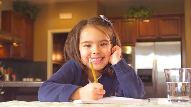 adorable little girl smiling - çalışma kitabı stok videoları ve detay görüntü çekimi