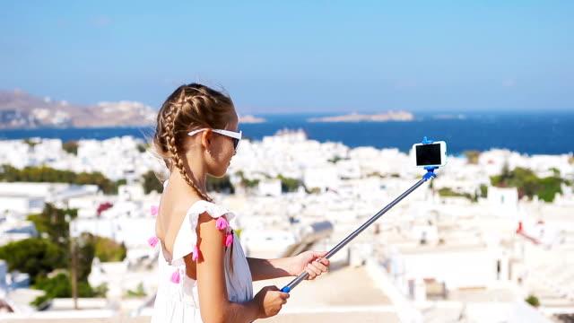 adorable little girl taking selfie photo background mykonos town in greece - isole egee video stock e b–roll