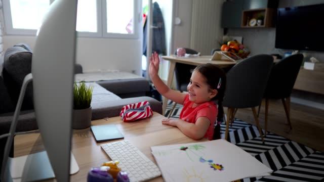 自宅の孤立でオンラインクラス中に彼女のお気に入りの先生に手を振る愛らしい小さな女の子 ビデオ