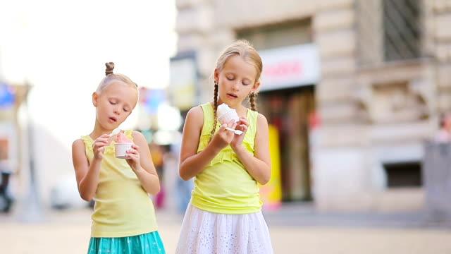 vídeos de stock, filmes e b-roll de meninas adoráveis que comem o gelado ao ar livre no verão. miúdos bonitos que apreciam o gelato italiano real perto de gelateria em roma - gelato