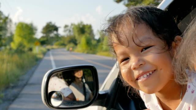 Adorable little girls is looking outside a window car while car moving on the way in the countryside. Concept of activity relaxing in evening. Slowmotion shot video