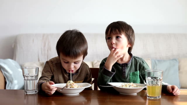 Adorable little kids, eating spaghetti at home, homemade pasta video