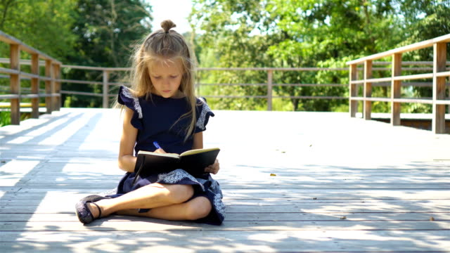 Adorable little school girl with notes and pencils outdoor. Back to school. video