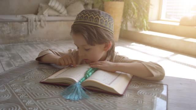 stockvideo's en b-roll-footage met aanbiddelijk moslimkind dat koran in gebedshoed en arabische kleren met rozenkranskralen leest en aan allah bidt - koran