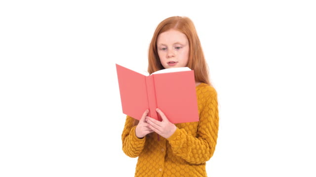 Adorable pensive school girl with long red hair wearing a bright orange t-shirt is reading a big book. Educational concept