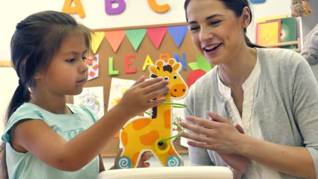Adorable preschool age girl plays with bead maze during day care Cute Hispanic little girl plays with a giraffe bead maze during her preschool class. The girl's attentive teacher smiles and claps as she encourages the girl to move the beads. child care stock videos & royalty-free footage