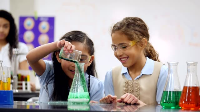 Adorable private elementary STEM school students conduct science experiment