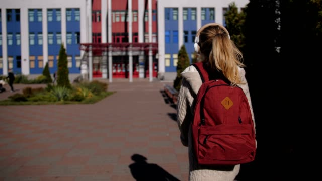 Adorable schoolgirl walking towards school building video