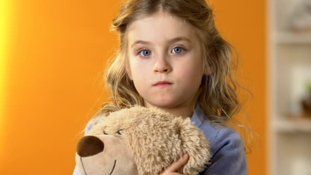 Adorable shy preschool girl hiding face in teddy bear, childhood psychology Adorable shy preschool girl hiding face in teddy bear, childhood psychology autism stock videos & royalty-free footage