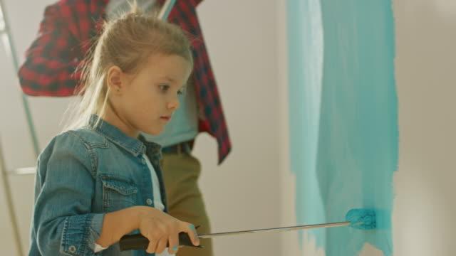 vidéos et rushes de adorable petite fille en jeans manteau est peindre un mur. elle peint avec rouleau qui est couvert de peinture bleue de lumière. peintures de père et fille. rénovation de la salle à la maison. - hlm