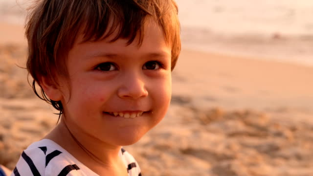 Adorable smiling kid on sandy beach