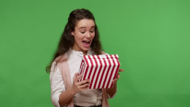 adorable teenage brunette girl taking long-awaited present for her birthday and jumping smiling shouting excitedly - indennità video stock e b–roll