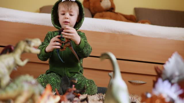 bedårande småbarn pojke i en dinosaurie kostym leker med sina dinosaurier - tyrannosaurus rex bildbanksvideor och videomaterial från bakom kulisserna