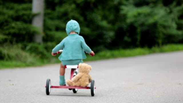 Adorable toddler boy with knitted outfit, riding tricycle on a quiet village street, summertime