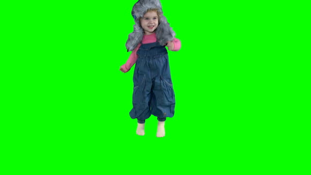 vídeos de stock e filmes b-roll de adorable toddler child girl jumping with warm winter hat isolated on green - roupa quente